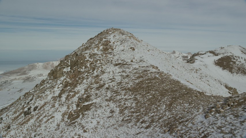 6K stock footage aerial video approach stony mountain peak with winter snow, Antelope Island, Utah Aerial Stock Footage | AX125_079