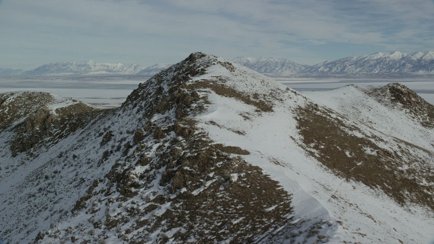6K stock footage aerial video of flying over rocky ridge with winter snow on Antelope Island, Utah Aerial Stock Footage | AX125_081
