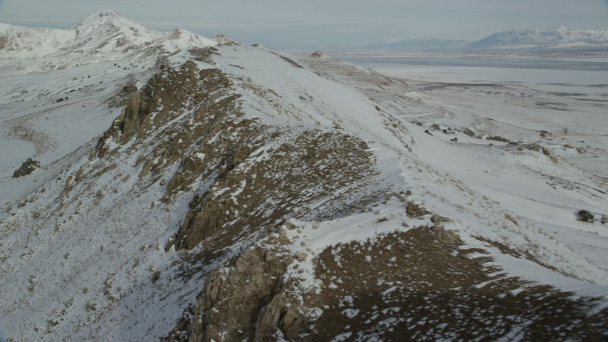 6K stock footage aerial video pan and fly over rocky mountain ridge with winter snow, Antelope Island, Utah Aerial Stock Footage | AX125_082