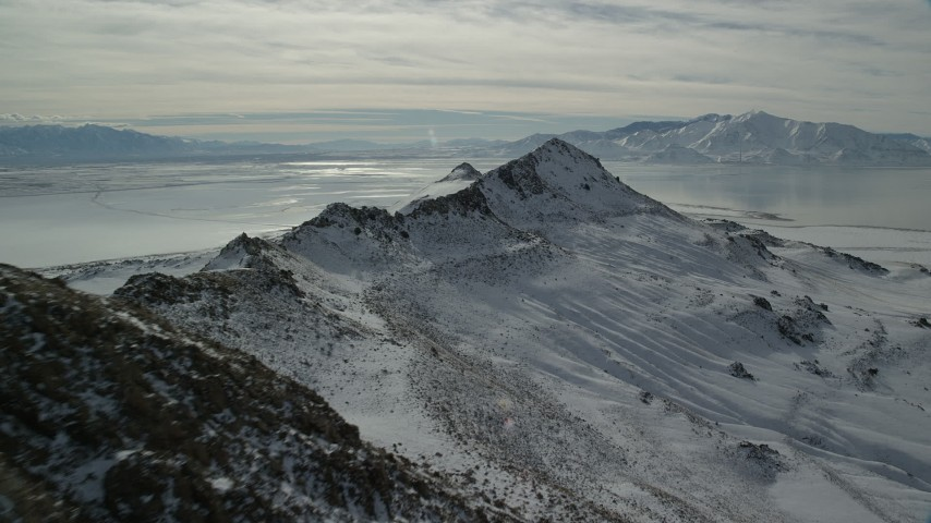 6K stock footage aerial video approach the end of a snowy mountain ridge in winter on Antelope Island, Utah Aerial Stock Footage | AX125_095