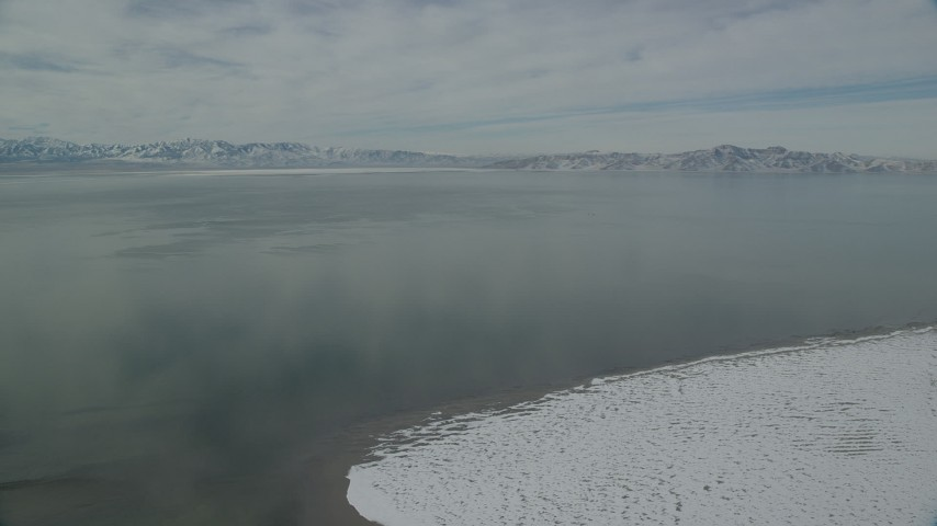 6K stock footage aerial video of Great Salt Lake with patches of ice and ringed by snow mountains, Utah Aerial Stock Footage | AX125_101