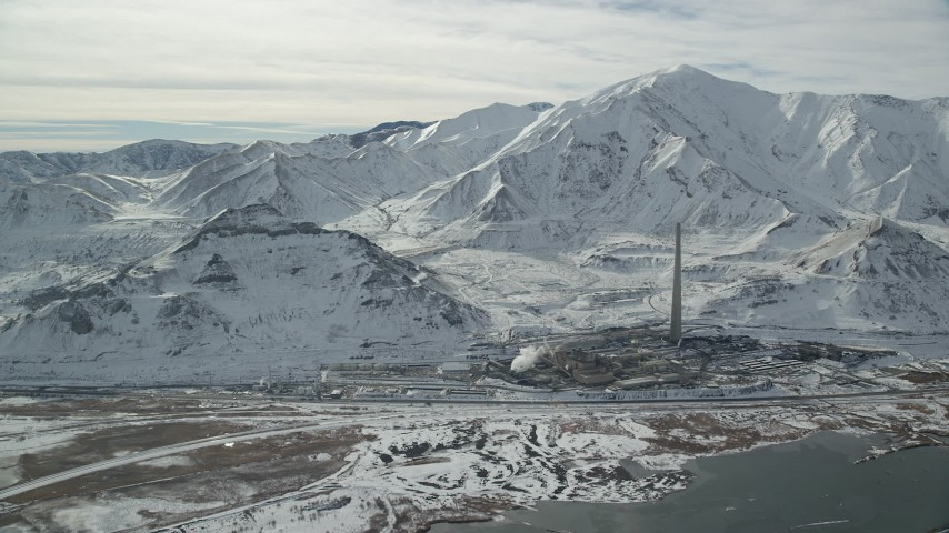 6K stock footage aerial video approach Kennecott Smokestack by Oquirrh Mountains in winter, Magna, Utah Aerial Stock Footage | AX125_109