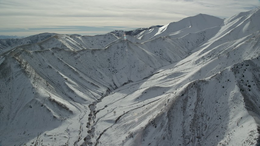 6K stock footage aerial video of steep snowy slopes of a mountain ridge of the Oquirrh Mountains, Utah Aerial Stock Footage | AX125_117