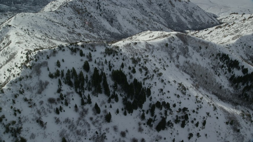 6K stock footage aerial video fly over and orbit snowy ridges and slopes in wintertime, Oquirrh Mountains, Utah Aerial Stock Footage | AX125_152