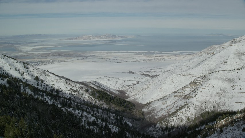 6K stock footage aerial video of Great Salt Lake seen from snowy Oquirrh Mountains, Utah Aerial Stock Footage   AX125_154