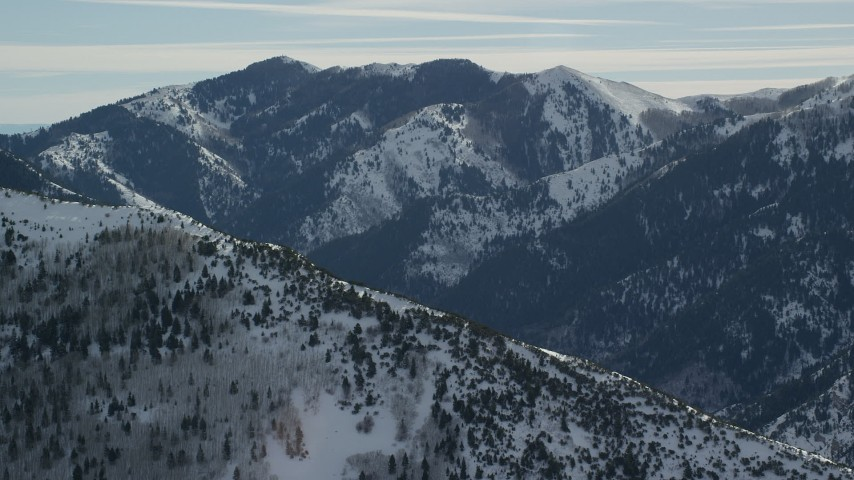 6K stock footage aerial video of snowy peak seen while orbiting Oquirrh Mountains ridge, Utah Aerial Stock Footage | AX125_174