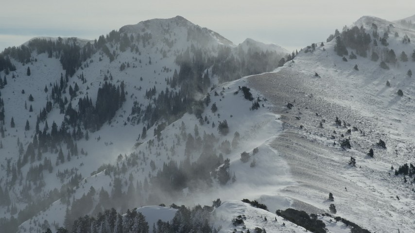 6K stock footage aerial video of Oquirrh Mountains with snowdrifts in wintertime, Utah Aerial Stock Footage | AX125_185