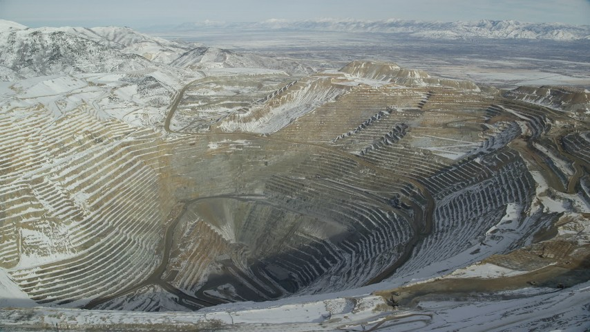 6K stock footage aerial video of orbiting Bingham Canyon Mine with light winter snow in Utah Aerial Stock Footage   AX125_232