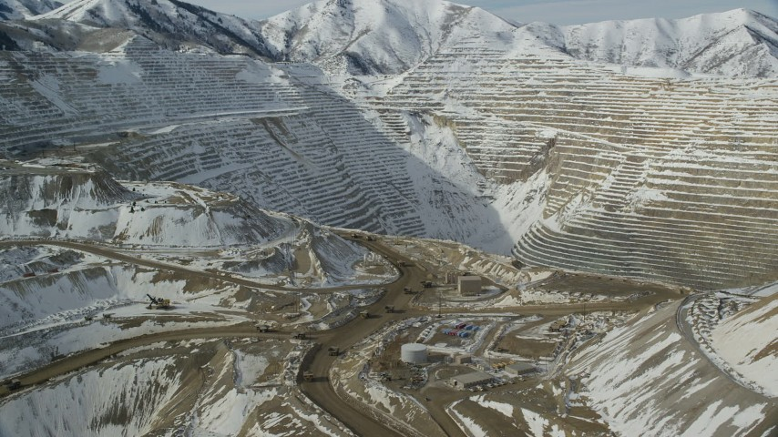 6K stock footage aerial video orbit the outer rim of the Bingham Canyon Copper Mine and gravel haulers in winter, Utah Aerial Stock Footage | AX125_239