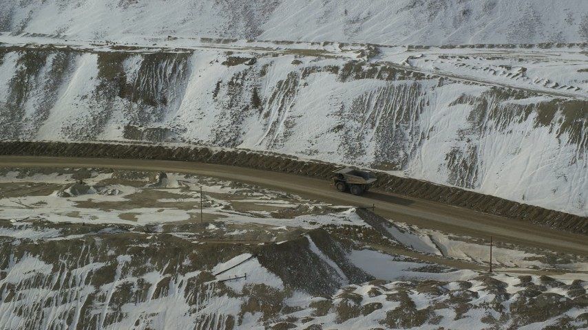6K stock footage aerial video of tracking a gravel hauler at the Bingham Canyon Mine in snowy Utah Aerial Stock Footage | AX125_241