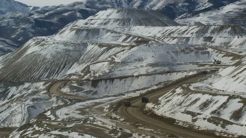 6K stock footage aerial video track gravel haulers at the Bingham Canyon Copper Mine with winter snow in Utah Aerial Stock Footage | AX125_242