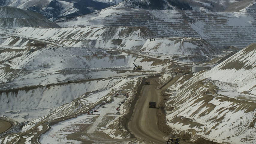 6K stock footage aerial video orbit Bingham Canyon Mine with gravel haulers and light snow, Utah Aerial Stock Footage | AX125_243
