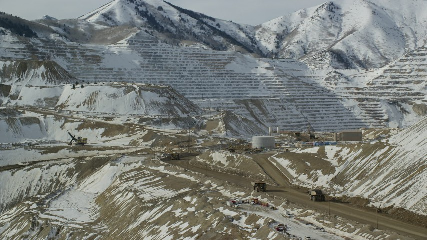 6K stock footage aerial video orbit gravel haulers at the giant Bingham Canyon Mine with winter snow, Utah Aerial Stock Footage | AX125_244