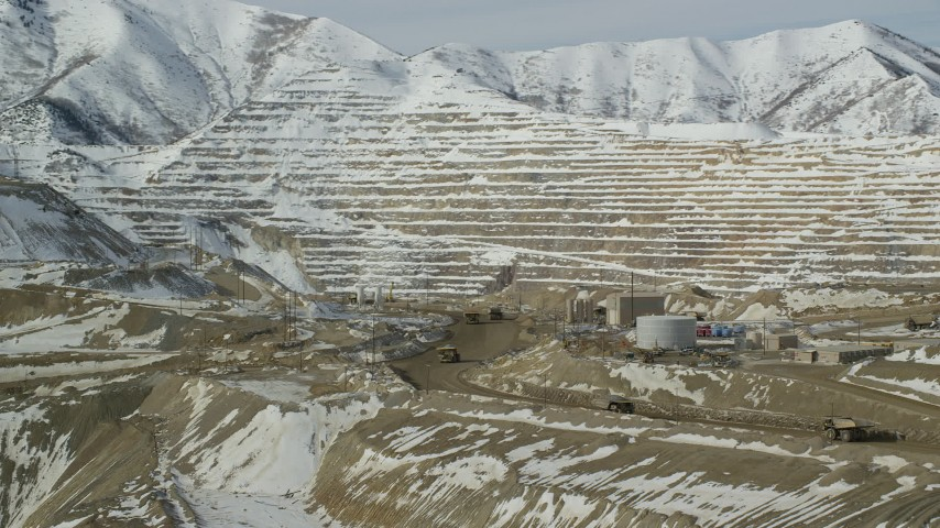 Orbit the Bingham Canyon Mine and Gravel Haulers on a Dirt Road in Winter Aerial Stock Footage | AX125_245