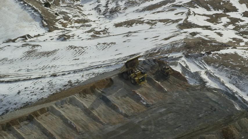 Gravel Hauler Dumping Dirt and Rocks at Bingham Canyon Mine, Utah, in Winter Aerial Stock Footage | AX125_252