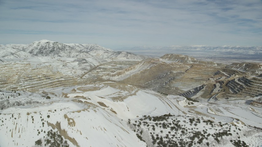 6K stock footage aerial video of a view across the Bingham Canyon Copper Mine with winter snow, Utah Aerial Stock Footage | AX125_256