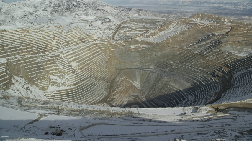 6K stock footage aerial video tilt to and orbit the Bingham Canyon Mine with winter snow, Utah Aerial Stock Footage | AX125_258