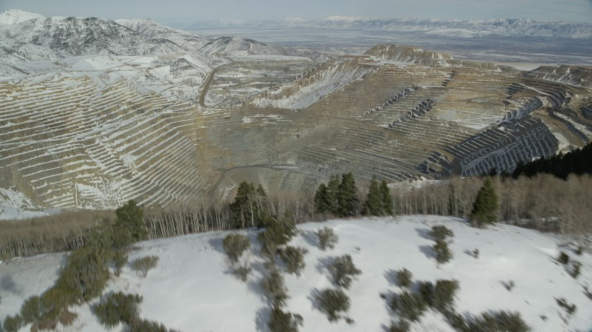 6K stock footage aerial video fly over snowy mountain ridge to reveal enormous open pit copper mine with winter snow, Utah Aerial Stock Footage | AX125_262