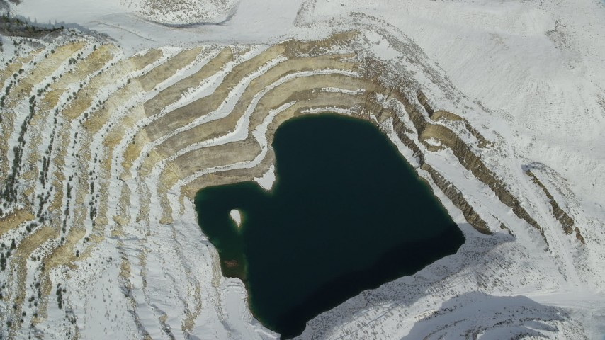 6K stock footage aerial video tilt to bird's eye view of a water-filled open pit mine with winter snow, Oquirrh Mountains, Utah Aerial Stock Footage | AX125_276