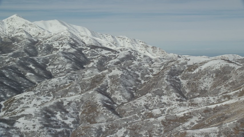 6K stock footage aerial video of flying by mountains with light snow near larger white peaks in winter, Oquirrh Mountains, Utah Aerial Stock Footage | AX125_284