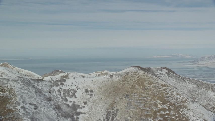 6K stock footage aerial video orbit snowy mountain ridge with view of Great Salt Lake in winter, Utah Aerial Stock Footage | AX125_287