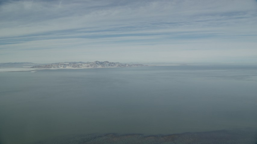 6K stock footage aerial video of the Great Salt Lake with winter ice and snow mountains on the shore, Utah Aerial Stock Footage | AX125_304