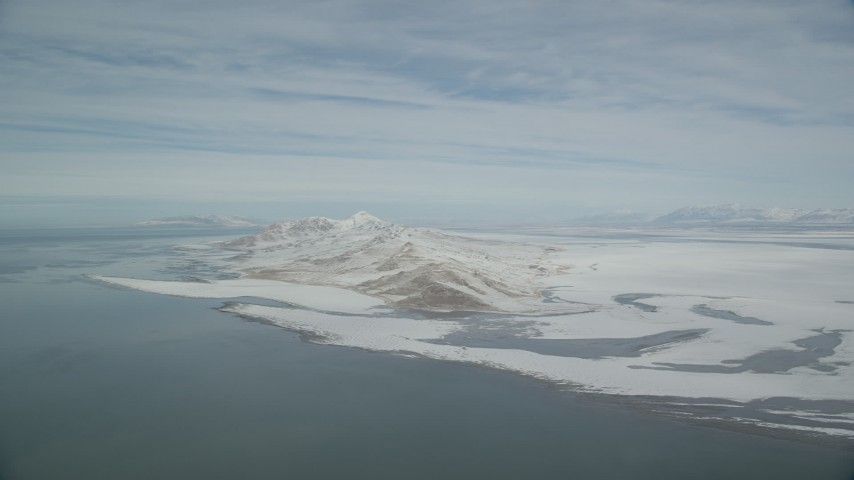 6K stock footage aerial video pan across Great Salt Lake to reveal snowy Antelope Island in winter, Utah Aerial Stock Footage | AX125_308