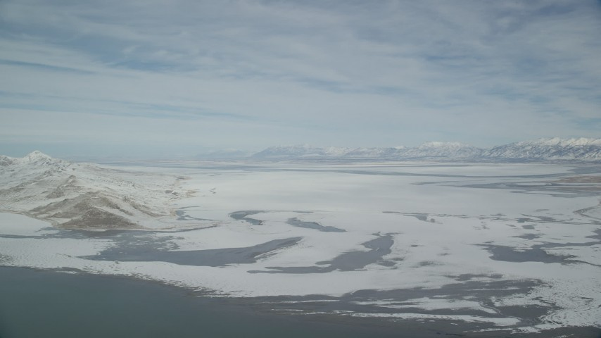 6K stock footage aerial video pan across Antelope Island and frozen marshlands in winter, Utah Aerial Stock Footage | AX125_309