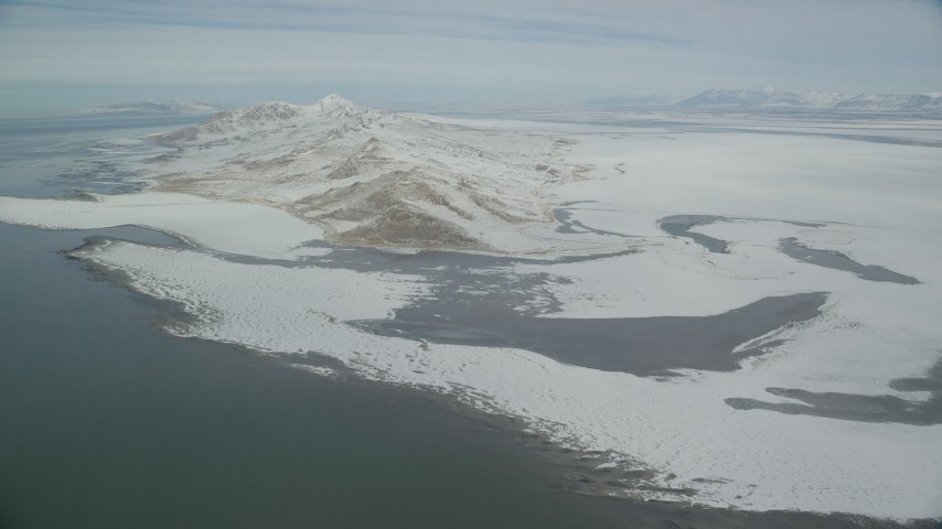 6K stock footage aerial video approach snowy mountains on the shore of Antelope Island, Utah Aerial Stock Footage | AX125_311