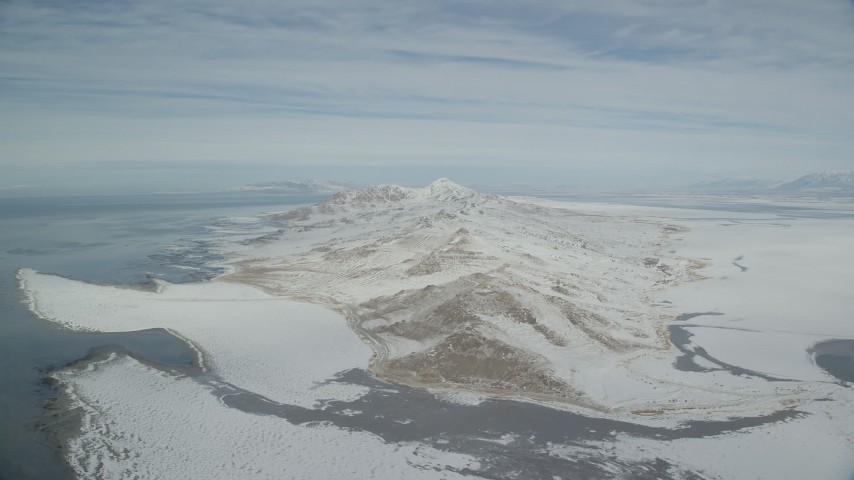 Slowly Approaching Antelope Island Snow Mountains in Wintertime Aerial Stock Footage | AX125_313