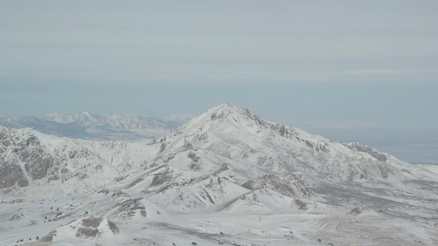 6K stock footage aerial video of orbiting a snowy Antelope Island mountain peak in winter, Utah Aerial Stock Footage | AX125_315