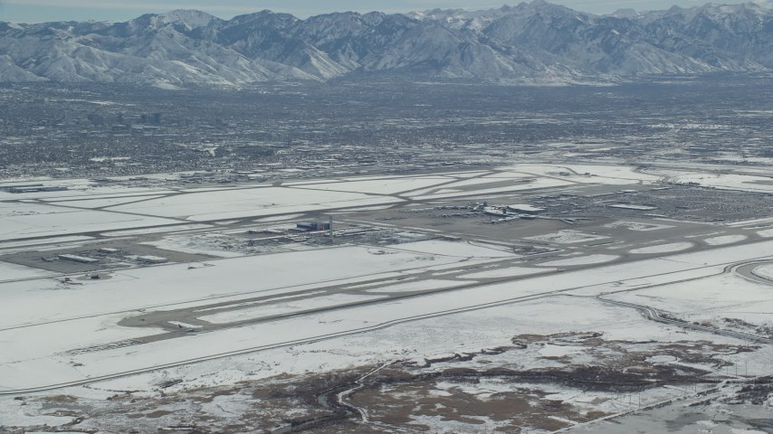 6K stock footage aerial video of slow approach to Salt Lake City International Airport with winter snow, Utah Aerial Stock Footage | AX125_322