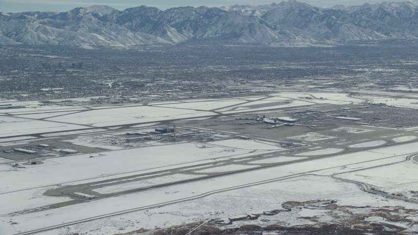 Slow Approach to SLC International Airport with White Winter Snow Aerial Stock Footage | AX125_323