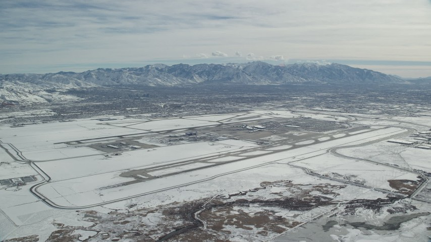6K stock footage aerial video of Salt Lake City International Airport in Utah with winter snow Aerial Stock Footage | AX125_324