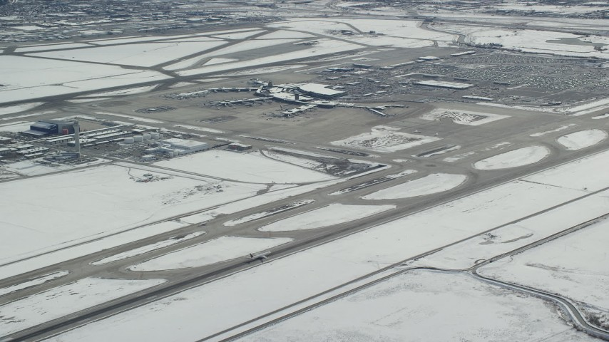 6K stock footage aerial video of tracking commercial jet on runway at SLC Airport with winter snow Aerial Stock Footage | AX125_325