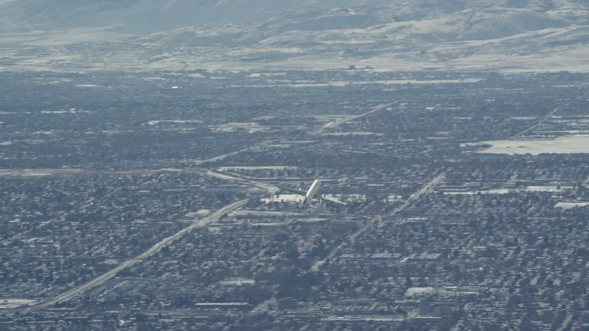 6K stock footage aerial video track airliner soaring over Salt Lake City in winter, Utah Aerial Stock Footage | AX125_328