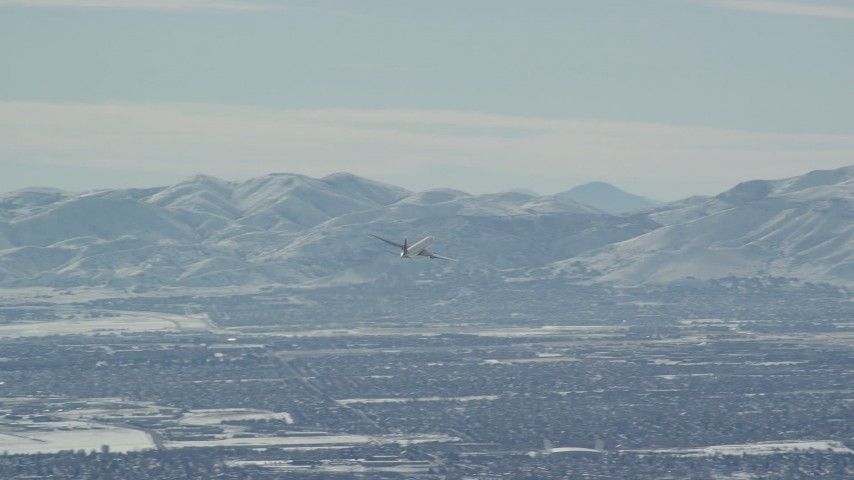 Track Commercial Airliner Flying Over Salt Lake City in Winter Aerial Stock Footage | AX125_329