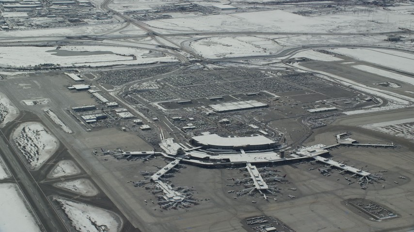 6K stock footage aerial video orbit terminals and parking lot at Salt Lake City Airport with winter snow, Utah Aerial Stock Footage | AX125_332
