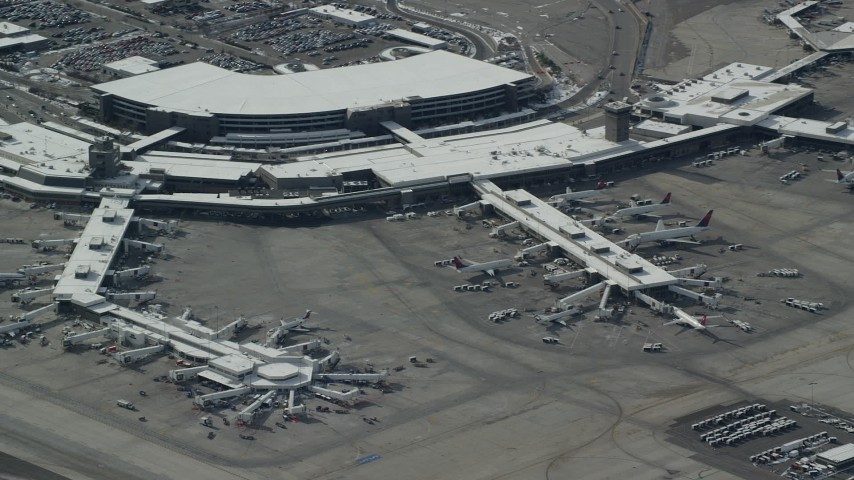 6K stock footage aerial video orbit airliners at the airport terminal of Salt Lake City Airport with winter snow, Utah Aerial Stock Footage | AX125_333