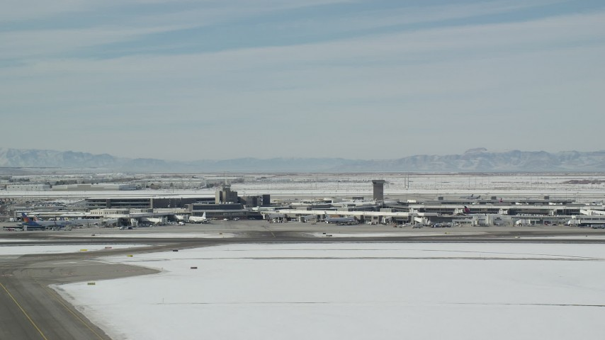 6K stock footage aerial video orbit of the main terminal at Salt Lake City Airport with winter snow, Utah Aerial Stock Footage | AX125_339