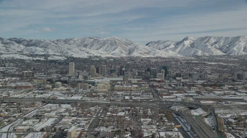 6K stock footage aerial video of downtown area of Salt Lake City and snowy mountains in winter, Utah Aerial Stock Footage | AX126_007