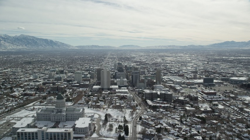 6K stock footage aerial video orbiting Downtown Salt Lake City and Utah State Capitol Building with winter snow Aerial Stock Footage | AX126_016