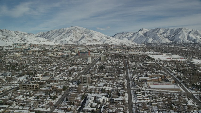 6K stock footage aerial video orbit suburban neighborhoods by snowy mountains in winter, Salt Lake City, Utah Aerial Stock Footage | AX126_045