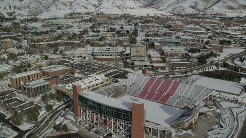 6K stock footage aerial video fly over Rice-Eccles Stadium and University of Utah buildings with winter snow, Salt Lake City Aerial Stock Footage | AX126_049