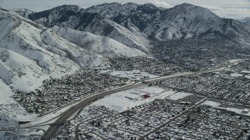 6K stock footage aerial video of suburban neighborhoods around Interstate 215 in snowy Salt Lake City, Utah Aerial Stock Footage | AX126_066