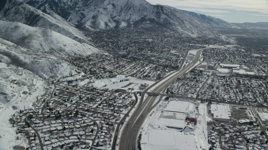 6K stock footage aerial video pan across Interstate 215 through suburbs in Salt Lake City with winter snow, Utah Aerial Stock Footage | AX126_067