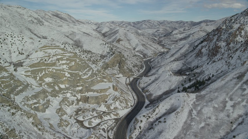 6K stock footage aerial video fly over Interstate 80 through Wasatch Range with winter snow, Utah Aerial Stock Footage | AX126_069