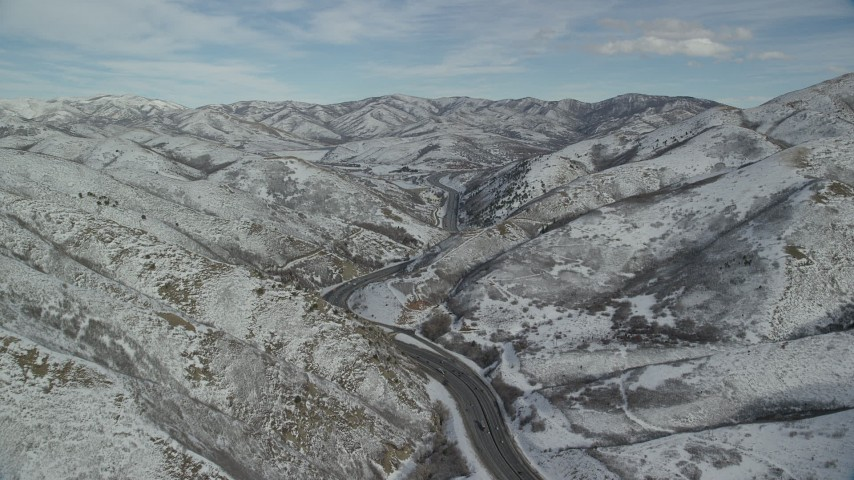 6K stock footage aerial video of following a mountain freeway through the Wasatch Range with winter snow, Utah Aerial Stock Footage | AX126_071