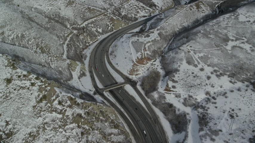 Bird's Eye of Light Traffic Rounding a Bend in Interstate 80 through Wasatch Range Aerial Stock Footage | AX126_072