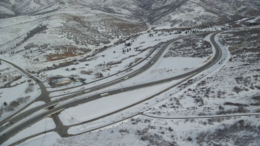 6K stock footage aerial video approach light traffic on Interstate 80 through the Wastach Range with snow, Utah Aerial Stock Footage | AX126_075